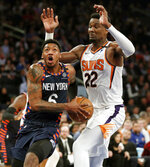 New York Knicks guard Elfrid Payton (6) drives around Phoenix Suns center Deandre Ayton (22) during the first half of an NBA basketball game in New York, Thursday, Jan. 16, 2020. (AP Photo/Kathy Willens)