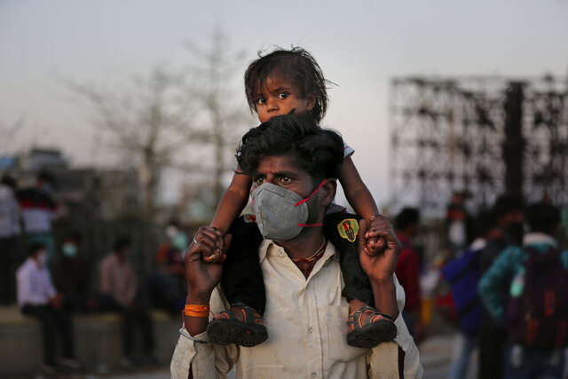 An Indian migrant worker carries a child on his shoulders as they wait for transportation to their village following a lockdown amid concern over spread of coronavirus in New Delhi, India, Saturday, March 28, 2020. Authorities sent a fleet of buses to the outskirts of India's capital on Saturday to meet an exodus of migrant workers desperately trying to reach their home villages during the world's largest coronavirus lockdown. Thousands of people, mostly young male day laborers but also families, fled their New Delhi homes after Prime Minister Narendra Modi announced a 21-day lockdown that began on Wednesday and effectively put millions of Indians who live off daily earnings out of work. (AP Photo/Altaf Qadri)