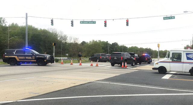 Vehicles are seen stopped at a roadblock, Friday, May 8, 2020, in Bear, Del. Delaware State Police were responding Friday to a report of shots being fired at Delaware's Veterans Memorial Cemetery, according to a police statement. A manhunt is reportedly underway for one or more suspects. (Esteban Parra/The News Journal via AP)