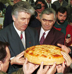 FILE - In this Jan. 9, 1996 file photo, Bosnian Serb wartime leader Radovan Karadzic, left, and Serb member of Bosnian Presidency Momcilo Krajisnik roll the cake, marking St. Stevan, Republic of Srpska patron-saint day, in the Bosnian town of Pale. The hospital in the northern Bosnian town of Banja Luka said Monday, Sept. 14, 2020, that Krajisnik, a former top wartime Bosnian Serb official who was convicted of war crimes by a U.N. court, died after contracting the new coronavirus. He was 75.  (AP Photo/Darko Vojinovic, File)