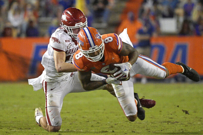 Arkansas defensive back Hudson Clark, left, tackles Florida wide receiver Trevon Grimes during the first half of an NCAA college football game, Saturday, Nov. 14, 2020, in Gainesville, Fla. (AP Photo/Phelan M. Ebenhack)