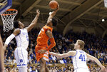 Duke's RJ Barrett (5) and Jack White (41) defend while Syracuse's Elijah Hughes (33) drives to the basket during the first half of an NCAA college basketball game in Durham, N.C., Monday, Jan. 14, 2019. (AP Photo/Gerry Broome)