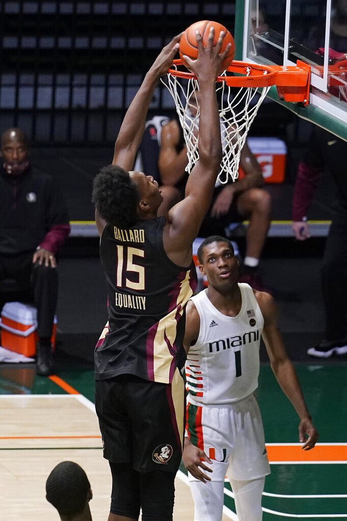 Florida State center Quincy Ballard (15) dunks the ball over Miami forward Anthony Walker (1) during the second half of an NCAA college basketball game, Wednesday, Feb. 24, 2021, in Coral Gables, Fla. (AP Photo/Marta Lavandier)