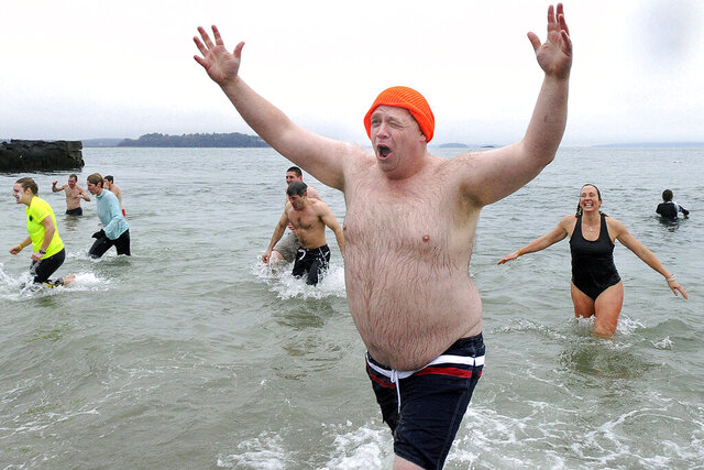 FILE - In this Dec. 31, 2011, file photo, David Greenham, of Readfield, Maine, reacts after taking a plunge with about 100 others participating in the annual Polar Bear Plunge at the East End Beach in Portland, Maine. The tradition of taking an icy plunge into the ocean to ring in 2021 is going virtual during the coronavirus pandemic. (John Patriquin/Portland Press Herald via AP)