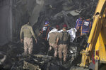 Security personnel retrieve a dead body from the  wreckage of a plane that crashed in a residential area of Karachi, Pakistan, May 22, 2020. An aviation official says a passenger plane belonging to state-run Pakistan International Airlines carrying more than 100 passengers and crew has crashed near the southern port city of Karachi. (AP Photo/Fareed Khan)