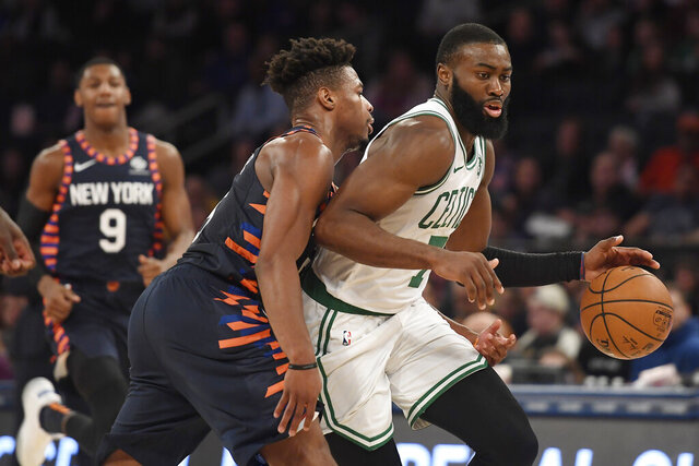 Boston Celtics guard Jaylen Brown (7) dribbles as New York Knicks guard Dennis Smith Jr. (5) defends during the second half of an NBA basketball game, Sunday, Dec. 1, 2019, in New York. (AP Photo/Sarah Stier)
