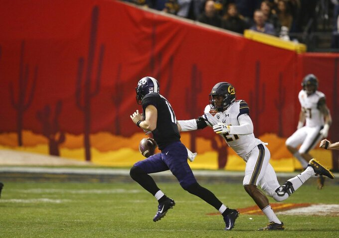 California safety Evan Rambo, right, reaches for TCU quarterback Grayson Muehlstein, left, during the first half of the Cheez-It Bowl NCAA college football game Wednesday, Dec. 26, 2018, in Phoenix. (AP Photo/Ross D. Franklin)