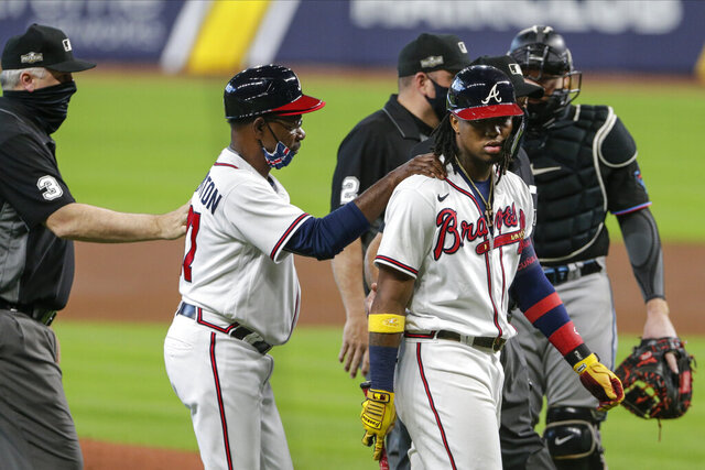 Atlanta Braves third base coach Ron Washington consoles Ronald Acuna Jr., center, during the third inning in Game 1 of a baseball National League Division Series against the Miami Marlins Tuesday, Oct. 6, 2020, in Houston. (AP Photo/Michael Wyke)