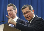 FILE - In this Feb. 15, 2019, file photo, California Attorney General Xavier Becerra, right, accompanied by Gov. Gavin Newsom, said California was probably suing President Donald Trump over his emergency declaration to fund a wall on the U.S.-Mexico border in Sacramento, Calif. Becerra filed a lawsuit Monday, Feb. 18, against Trump's emergency declaration to fund a wall on the U.S.-Mexico border. Becerra released a statement Monday, saying 16 states — including California — allege the Trump administration's action violates the Constitution.  (AP Photo/Rich Pedroncelli, File)