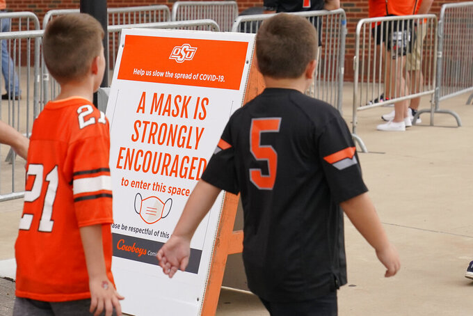 Two young fans walk past a sign encouraging mask wearing outside Boone Pickens Stadium before an NCAA college football game between Missouri State and Oklahoma State, Saturday, Sept. 4, 2021, in Stillwater, Okla. (AP Photo/Sue Ogrocki)