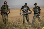 Israeli police sappers remove a rocket fired from the Gaza Strip in farmland near the Israel Gaza border, Wednesday, Nov. 13, 2019. Israeli military said more than 250 rockets have been fired at Israeli communities since the violence erupted following an Israeli airstrike that killed a senior Islamic Jihad commander. (AP Photo/Tsafrir Abayov)