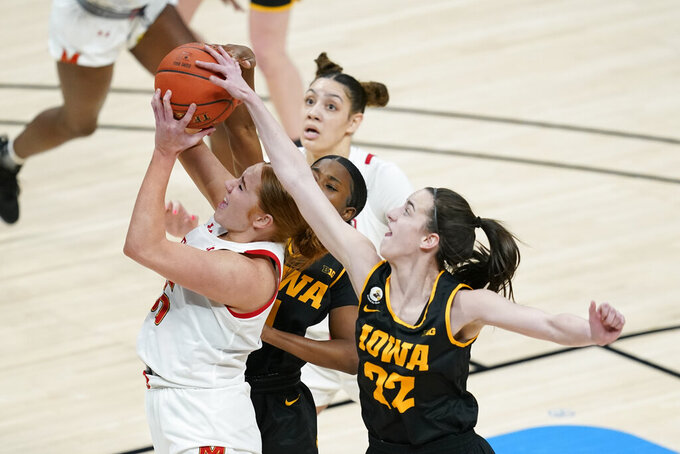 Maryland's Chloe Bibby (55) shoots against Iowa's Tomi Taiwo (1) and Caitlin Clark (22) during the first half of an NCAA college basketball championship game at the Big Ten Conference tournament, Saturday, March 13, 2021, in Indianapolis. (AP Photo/Darron Cummings)