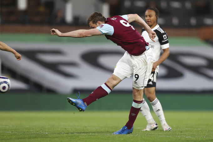 Burnley's Chris Wood, left, scores his side's second goal during the English Premier League soccer match between Fulham and Burnley at the Craven Cottage Stadium in London, Monday, May 10, 2021. (Clive Rose/Pool via AP)