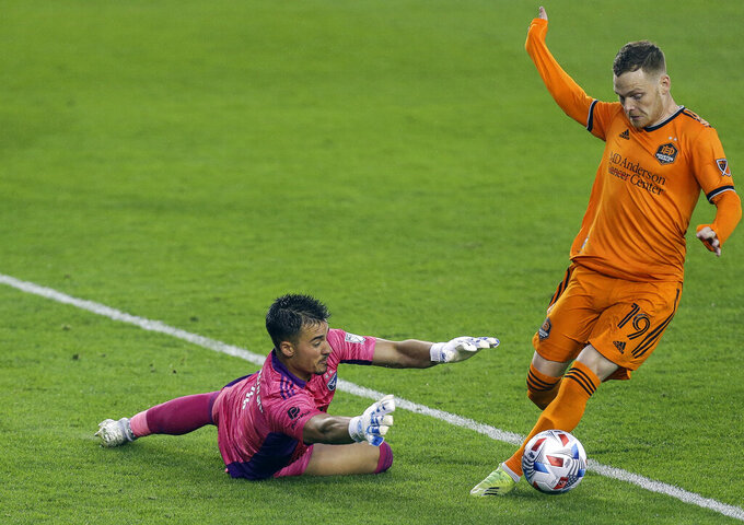 San Jose Earthquakes goalkeeper JT Marcinkowski (1) makes a save against Houston Dynamo FC forward Tyler Pasher (19) during the first half of an MLS soccer game at BBVA Stadium on Friday, April 16, 2021, in Houston. (Godofredo A. Vásquez/Houston Chronicle via AP)