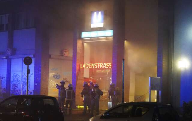 Firefighters extinguish a fire in the row of shops in the Uncle Tom's Hut subway station in Berlin, Germany, Sunday, Nov. 15, 2020. Four people have been injured, one of them severely, when a fire broke out in a subway station in Berlin. The German news agency dpa reported Monday that the fire broke out late Sunday and 120 firefighters were still fighting the flames Monday morning, but said the fire was mostly under control. (Joerg Carstensen/dpa via AP)