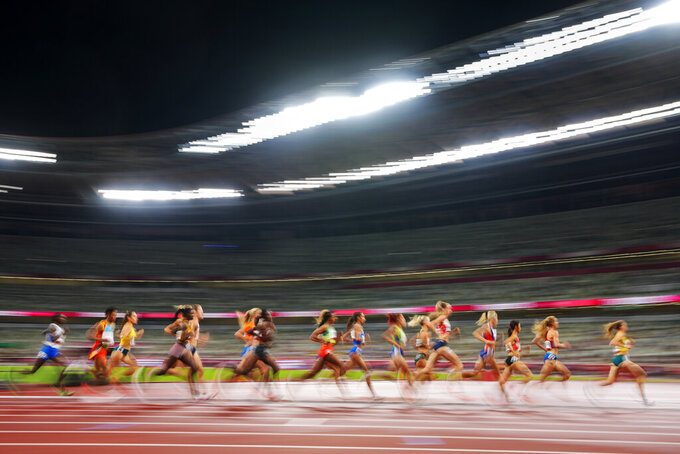 Runners compete in a heat of the women's 5,000-meter run at the 2020 Summer Olympics, Friday, July 30, 2021, in Tokyo. (AP Photo/Petr David Josek)