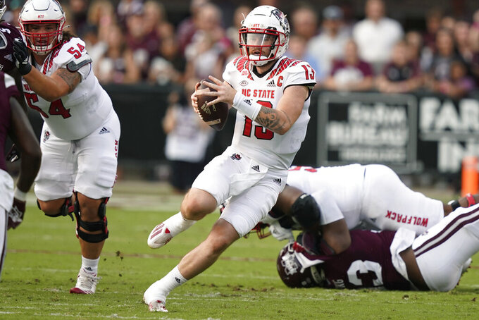 North Carolina State quarterback Devin Leary (13) runs upfield against the Mississippi State defense during the first half of an NCAA college football game in Starkville, Miss., Saturday, Sept. 11, 2021. (AP Photo/Rogelio V. Solis)