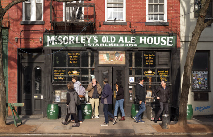 In this Dec. 27, 2019 photo, people come and go from McSorley's Old Ale House in New York. Located in Manhattan's Lower East Side, McSorley's opened in the mid-19th century, functioned as a speakeasy during Prohibition, and continues in operation today. (AP Photo/Mark Lennihan)