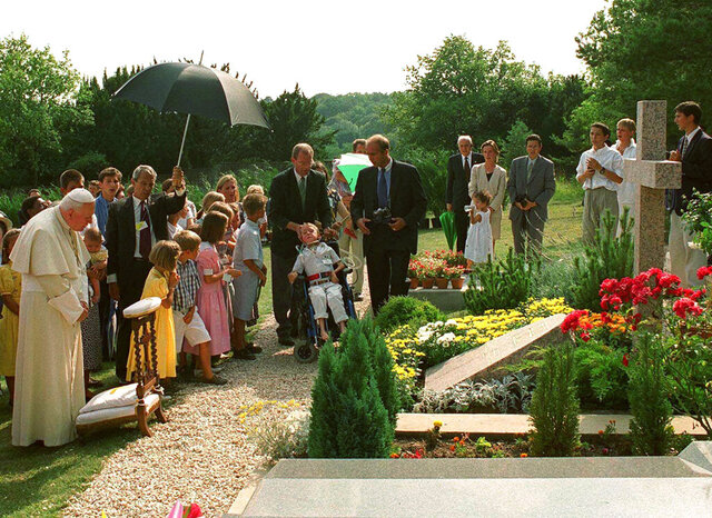"FILE - In this Aug.22, 1997 file photo, Pope John Paul II meditates by the grave of his former friend geneticist Jerome Lejeune, during a private visit to the Chalo-Saint-Mars cemetery near Paris. Pope Francis on Thursday, Jan. 21, 2021, approved the ""heroic virtues"" of Dr. Jerome Lejeune, who discovered the genetic basis of Down syndrome, lived from 1926-1994 and was particularly esteemed by St. John Paul II for his anti-abortion stance. (AP Photo/Arturo Mari/file)"
