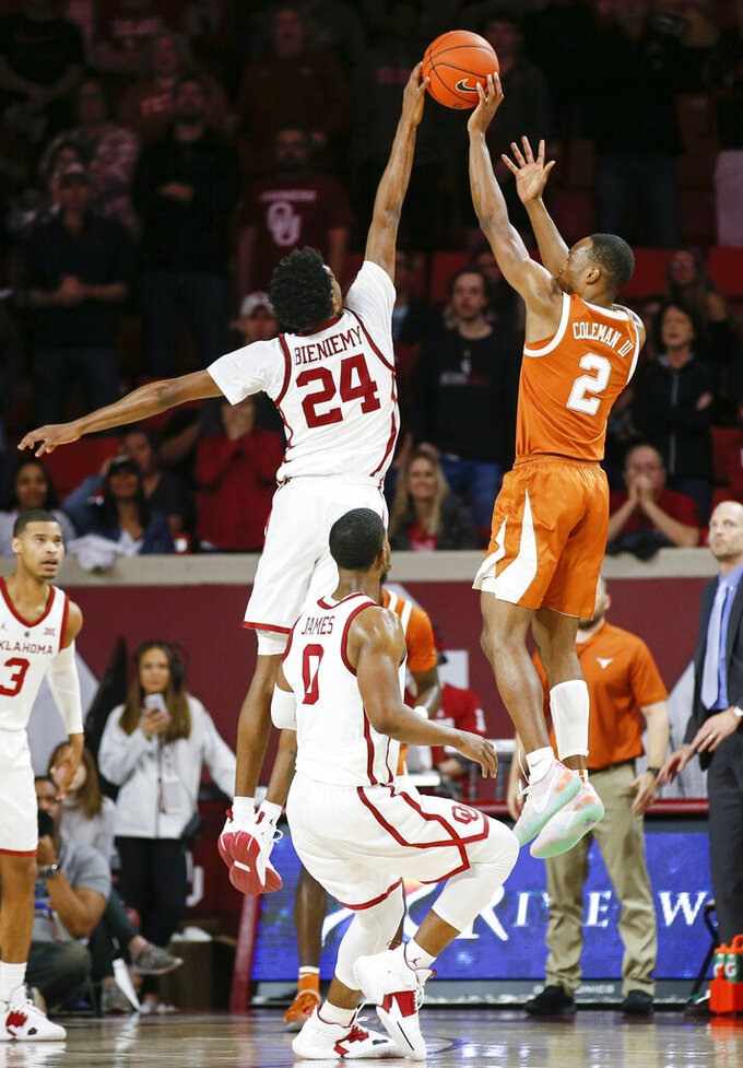 Oklahoma's Jamal Bieniemy (24) blocks a last-second shot by Texas' Matt Coleman III (2) during the second half of an NCAA college basketball game in Norman, Okla., Saturday, Feb. 23, 2019. Oklahoma won 69-67. (Nate Billings/The Oklahoman via AP)