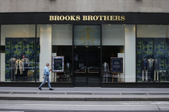 """FILE - Pedestrians wearing protective masks walk past a Brooks Brothers location on July 8, 2020, in New York. A retail venture owned by licensing company Authentic Brands Group and mall owner Simon Property Group has agreed to buy Brooks Brothers for $305 million. The offer from Sparc Group LLC, announced late Thursday, July 23, has been designated as a """"stalking horse"""" and therefore subject to court approval and any higher or better offers as part of the company's ongoing auction process.  (AP Photo/Frank Franklin II, File)"""