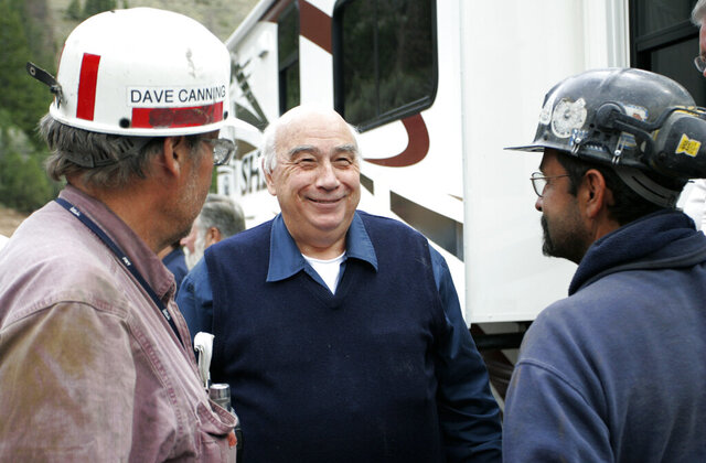 Robert Murray, center, chief executive of Murray Energy Corp., smiles while talking to Dave Canning, left, and Mike Glassom, right, two miners in charge of drilling bore holes into the Crandall Canyon Mine, before a news conference northwest of Huntington Utah, Sunday, Aug, 26, 2007. Murray, the founder and former president and CEO of a major U.S. coal operator that recently emerged from federal bankruptcy, has retired as chairman of the company's board. Murray ended a six-decade career by announcing his retirement Monday, Oct. 19, 2020 as board chairman of American Consolidated Natural Resource Holdings Inc. (AP Photo/Kenny Crookston)