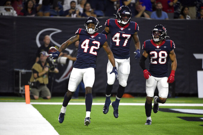 Houston Texans defensive back Jermaine Ponder (42) celebrates with Austin Exford (47) and Xavier Crawford (28) after intercepting a pass against the Los Angeles Rams during the first half of a preseason NFL football game Thursday, Aug. 29, 2019, in Houston. (AP Photo/Eric Christian Smith)