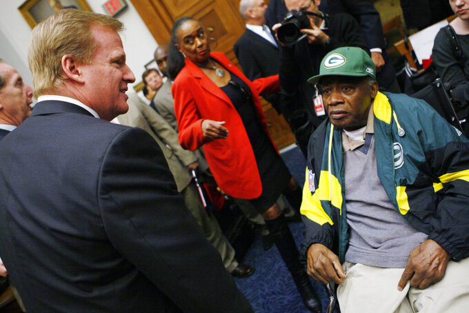 FILE - In this Wednesday, Oct. 28, 2009 file photo, NFL Commissioner Roger Goodell, left, meets former Green Bay Packers player Willie Wood, on Capitol Hill in Washington,  during a House Judiciary Committee hearing on legal issues relating to football head injuries. Pro Football Hall of Famer Willie Wood, captain of the 1959 USC football team who played in the first 2 Super Bowls, died today, Monday, Feb. 3, 2020 of natural causes in Washington, D.C.  He was 83.(AP Photo/Charles Dharapak, File)
