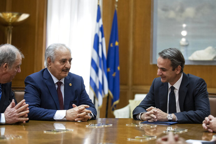 Greek Prime Minister Kyriakos Mitsotakis, right, meets with Libyan Gen. Khalifa Hifter, second left, in Athens, Friday, Jan. 17, 2020.  The commander of anti-government forces in war-torn Libya has begun meetings in Athens in a bid to counter Turkey's support for his opponents. (AP Photo/Petros Giannakouris)