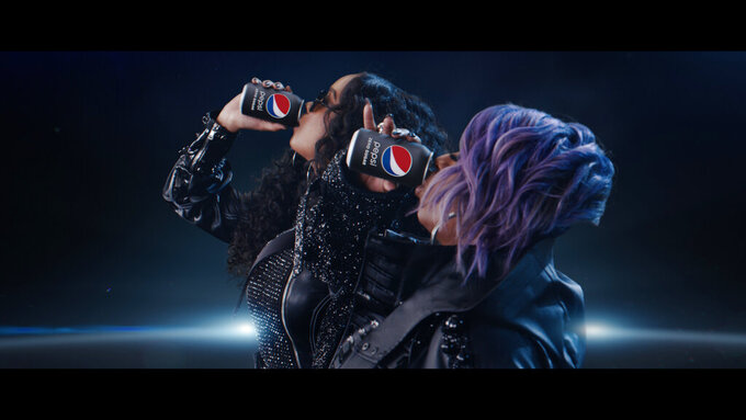 "This undated image provided by PepsiCo shows Missy Elliott, right, and H.E.R. in a scene from the company's 2020 Super Bowl NFL football spot. Pepsi tries to reignite the Cola Wars with Missy Elliott and H.E.R. performing an updated version of ""Paint it Black"" that starts with a red cola can that looks like a Coke changing into a black can of Pepsi Zero Sugar to the lyrics of ""I see a red door and I want it painted black."" (PepsiCo via AP)"