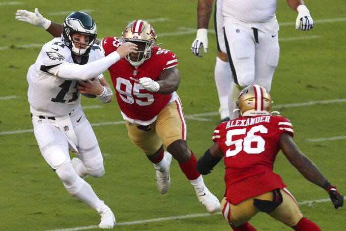 Philadelphia Eagles quarterback Carson Wentz (11) runs against San Francisco 49ers defensive end Kentavius Street (95) and outside linebacker Kwon Alexander (56) during the first half of an NFL football game in Santa Clara, Calif., Sunday, Oct. 4, 2020. (AP Photo/Jed Jacobsohn)