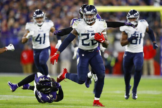 El running back Derrick Henry (22) de los Titans de Tennesse deja atrás al safety Chuck Clark (36) de los Ravens de Baltimore en el partido de la ronda divisional de los playoffs de la NFL, el sábado 11 de enero de 2020. (AP Foto/Julio Cortez)