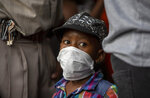 A young boy wearing a face mask to protect against coronavirus, with his father stands in a queue to shop in Soweto, South Africa, Thursday, March 26, 2020. In hours South Africa goes into a nationwide lockdown for 21-days in an effort to mitigate the spread to the coronavirus.  (AP Photo/Themba Hadebe)