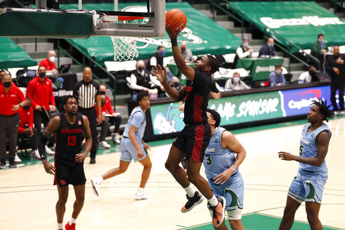 Houston guard Jamal Shead (1) drives to the basket past Tulane forward Tylan Pope (3) during the second half of an NCAA college basketball game in New Orleans, Thursday, Jan. 28, 2021. Houston won 83-60. (AP Photo/Tyler Kaufman)