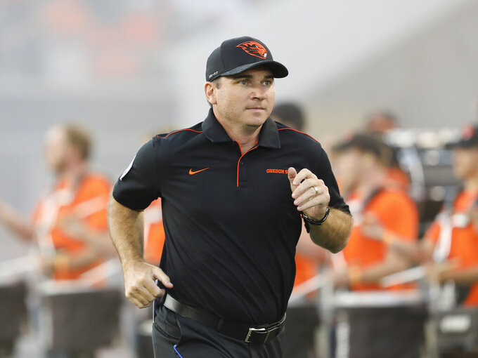 FILE - In this Aug. 30, 2019, file photo, Oregon State coach Jonathan Smith runs onto the field for the team's NCAA college football game against Oklahoma State, in Corvallis, Ore. Oregon State coach Jonathan Smith has received a three-year contract extension that would keep him with the Beavers through the 2025 season.  (AP Photo/Amanda Loman, File)