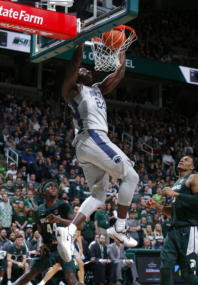 Penn State's Mike Watkins dunks on an alley-oop, over Michigan State's Gabe Brown, left, and Xavier Tillman, right, during the first half of an NCAA college basketball game Tuesday, Feb. 4, 2020, in East Lansing, Mich. (AP Photo/Al Goldis)