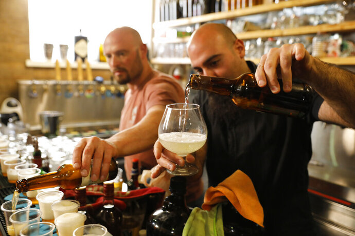Craft brewer from Biratenu, the Jerusalem Beer Center, Shmuel Naky, right, pours beer during a press conference in Jerusalem, Wednesday, May 22, 2019. Israeli researchers raised a glass Wednesday to celebrate a long-brewing project of making beer and mead using yeasts extracted from ancient clay vessels -- some over 5,000 years old. Archaeologists and microbiologists teamed up to study yeast colonies found in microscopic pores in ancient pottery fragments. (AP Photo/Sebastian Scheiner)