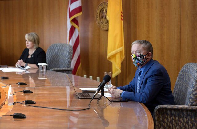 Health and Human Services Secretary Dr. David Scrase gives an update on the COVID-19 outbreak in the state as New Mexico Gov. Michelle Lujan Grisham, left, listens during a news conference in the state Capitol in Santa Fe, N.M., Wednesday, April 15, 2020. (Eddie Moore/The Albuquerque Journal via AP, Pool)