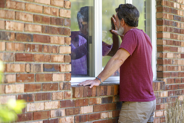 Jack Campise talks with his mother, Beverly Kearns, through her apartment window at the Kimberly Hall North nursing home, Thursday, May 14, 2020 in Windsor, Conn. The coronavirus has had no regard for health care quality or ratings as it has swept through nursing homes around the world, killing efficiently even in highly rated care centers. Preliminary research indicates the numbers of nursing home residents testing positive for the coronavirus and dying from COVID-19 are linked to location and population density — not care quality ratings. (AP Photo/Chris Ehrmann