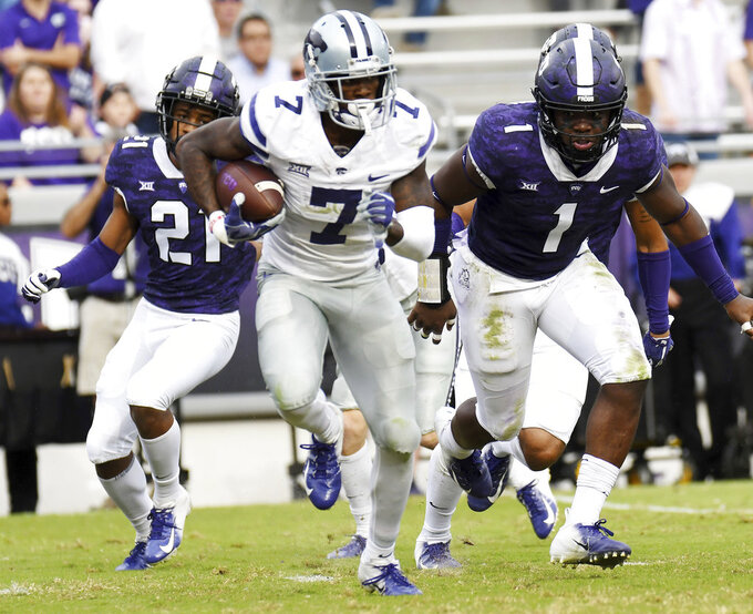 Kansas State's Issiah Zuber, center is chased by TCU's Noah Daniels, left and Jawuan Johnson during a punt return in the second quarter of an NCAA college football game Saturday, Nov. 3, 2018, in Fort Worth, Texas. (Bob Haynes/Star-Telegram via AP)