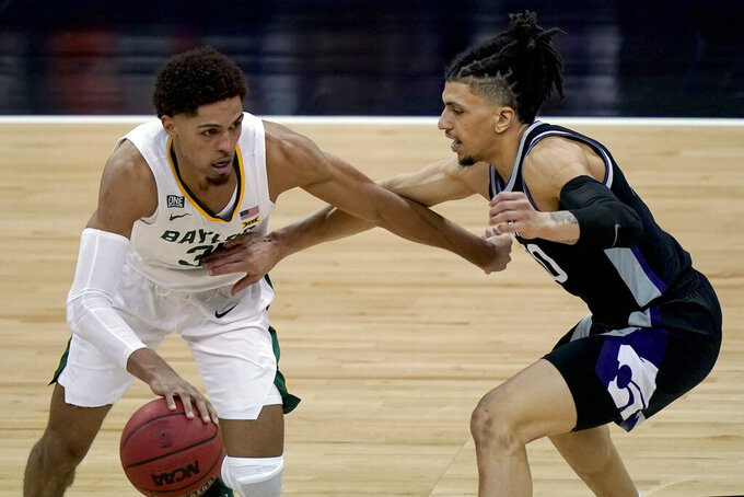 Baylor's MaCio Teague, left, is pressured by Kansas State's Mike McGuirl during the second half of an NCAA college basketball game in the second round of the Big 12 men's tournament in Kansas City, Mo., Thursday, March 11, 2021. (AP Photo/Charlie Riedel)