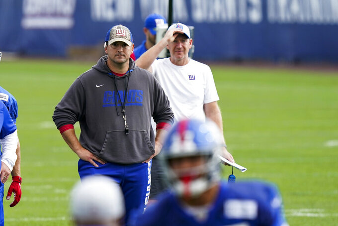 New York Giants head coach Joe Judge, background left, looks on at NFL football training camp, Wednesday, July 28, 2021, in East Rutherford, N.J. (AP Photo/Corey Sipkin)