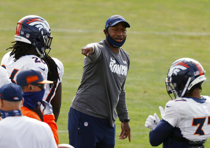 FILE - In this Friday, Aug. 28, 2020 file photo, Denver Broncos defensive backs coach Renaldo Hill takes part in drills during an NFL football practice in Englewood, Colo. Renaldo Hill is getting his first opportunity to be a defensive coordinator, but he won't be thrown into the deep end of the pool yet. Chargers head coach Brandon Staley will call the plays during games, allowing Hill to be able to progress at his own pace. (AP Photo/David Zalubowski, File)