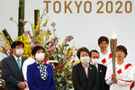 FILE -  In this March 25, 2021, file photo, Tokyo Gov. Yuriko Koike, third from left, and Tokyo 2020 Organizing Committee President Seiko Hashimoto, fourth from left, wearing face masks, attend the Tokyo 2020 Olympic Torch Relay Grand Startin Naraha, Fukushima prefecture, northeastern Japan. The torch relay for the postponed Tokyo Olympics began its 121-day journey across Japan on March 25 and is headed toward the opening ceremony in Tokyo on July 23. (Kim Kyung-Hoon/Pool Photo via AP, File)