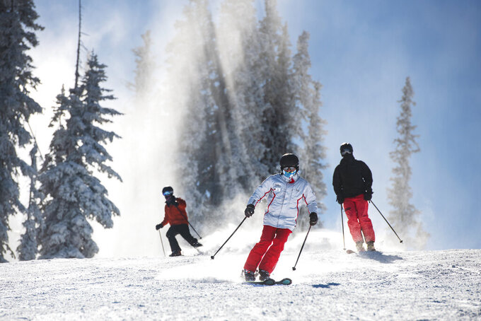 FILE - In this Nov. 25, 2020, file photo, skiers enjoy freshly-made snow on Aspen Mountain's opening day of the ski season in Aspen, Colo. Ski areas across the United States experienced a strong rebound this winter season despite public health restrictions put in place amid the coronavirus pandemic. Skier visits to U.S. resorts totaled 59 million this winter season, the fifth best on record, according to the Colorado-based National Ski Areas Association. A visit is considered the use of a lift ticket for any part of the day. (Kelsey Brunner/The Aspen Times via AP, File)