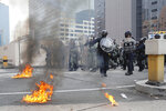 Riot police gather around small fires during a protest in Hong Kong, Saturday, Aug. 24, 2019. Chinese police said Saturday they released an employee at the British Consulate in Hong Kong as the city's pro-democracy protesters took to the streets again, this time to call for the removal of