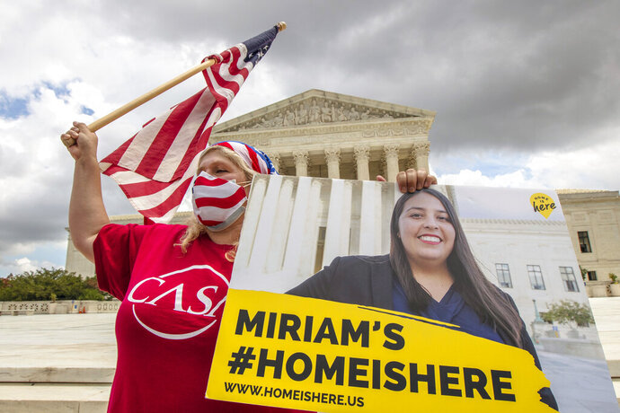 Ivania Castillo from Prince William County, Va., holds a banner to show her support for dreamer Miriam from California, as she joins Deferred Action for Childhood Arrivals (DACA) recipients celebrate in front of the U.S. Supreme Court after the Supreme Court rejected President Donald Trump's bid to end legal protections for young immigrants, Thursday, June 18, 2020, in Washington. (AP Photo/Manuel Balce Ceneta)