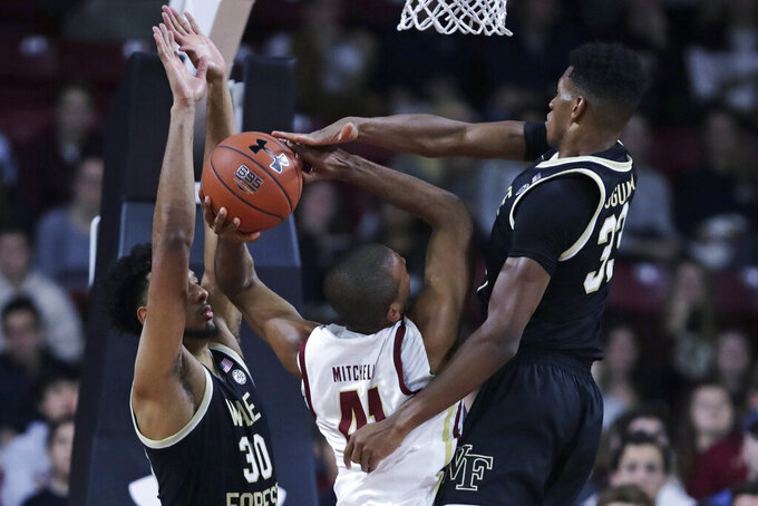 Wake Forest forward Ody Oguama, right, fouls Boston College forward Steffon Mitchell (41) during the first half of an NCAA college basketball game in Boston, Wednesday, Nov. 6, 2019. At left is Wake Forest center Olivier Sarr (30). (AP Photo/Charles Krupa)