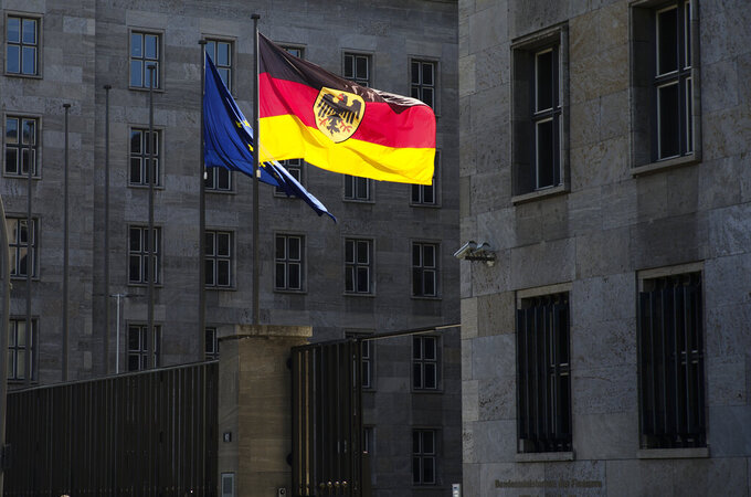 The German and European flag waves in front of German Finance Ministry in Berlin, Germany, Thursday, Sept. 9, 2021. Investigators have carried out searches at the German finance and justice ministries in a probe of suspected obstruction of justice by employees of a unit of the country's customs service that fights money laundering. Word of the searches come just over two weeks ahead of a parliamentary election in which Finance Minister Olaf Scholz is running for chancellor. (AP Photo/Markus Schreiber)