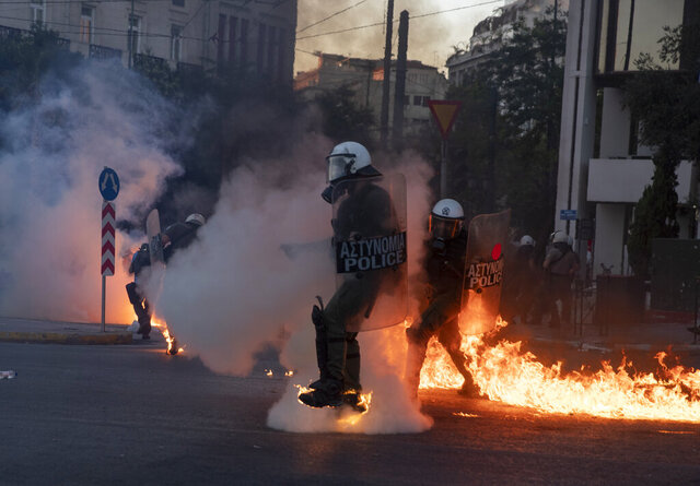 Riot police officers try to avoid patrol bombs thrown by protesters outside the Greek Parliament during a protest against new protest law in Athens, on Thursday, July 9, 2020. Violence has broken out in Athens during a mass demonstration against plans to curb public protests. (AP Photo/Petros Giannakouris)